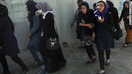 Roshan mobile company employees leave the site of the attack in Kabul on Wednesday.