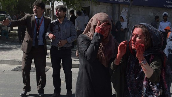 Women covered in blood stand dazed in the aftermath of the attack near Kabul