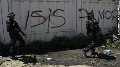 Philippine soldiers walk past Islamic State (IS) group graffiti in Marawi on the southern island of Mindanao on May 31, 2017, as fighting between government forces and Muslim militants rages on the ninth day. Philippine security forces have killed 89 Islamist militants during more than a week of fighting in a southern city but the gunmen are still offering strong resistance and holding hostages, the military said on May 31. / AFP PHOTO / TED ALJIBE        (Photo credit should read TED ALJIBE/AFP/Getty Images)