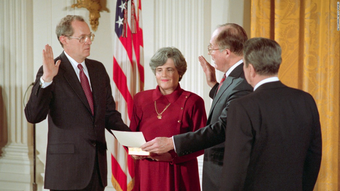 Kennedy is joined by his wife as he is sworn in by Chief Justice William Rehnquist on February 18, 1988. Reagan is on the right.