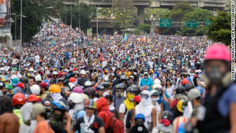 "Opposition activists march during a protest against the government of President Nicolas Maduro in Caracas on May 31, 2017.  Venezuelan authorities on Wednesday began signing up candidates for a planned constitutional reform body, a move that has inflamed deadly unrest stemming from anti-government protests. Opponents of socialist President Nicolas Maduro say he aims to keep himself in power by stacking the planned ""constituent assembly"" with his allies.  / AFP PHOTO / FEDERICO PARRA        (Photo credit should read FEDERICO PARRA/AFP/Getty Images)"