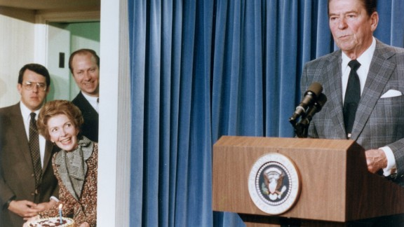 4th February 1983:  US President Ronald Reagan stands behind a lectern as First Lady Nancy Reagan stands in a side doorway, planning to surprise the President with a birthday cake, at the White House, Washington, DC. Two men stand behind the First Lady.
