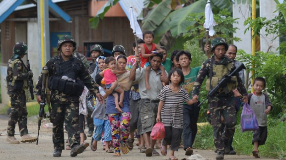 Philippine troops escort rescued civilians at a village on the outskirts of Marawi on May 31.