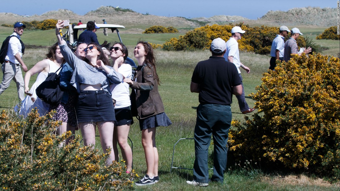 Young women try to get a selfie with former US President Barack Obama as he plays a round of golf in St. Andrews, Scotland, on Friday, May 26.