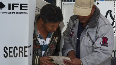 Citizens check their ballots before casting their votes at polling station in a school in San Lorenzo Tlacoyucan, in Mexico City, on election day on July 1, 2012. Almost 80 million Mexicans are expected to vote in Mexico's presidential election, in which voters exhausted by violence seem prepared to bring the PRI, the party that ran the country for seven decades, back to office. Mexican presidents are elected by simple majority for six-year terms and are banned from running for re-election. AFP PHOTO/OMAR TORRES        (Photo credit should read OMAR TORRES/AFP/GettyImages)