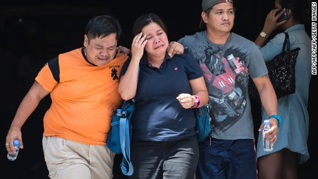 Relatives of a victim in the attack on the Resorts World Manila cry Friday outside the Philippine complex.