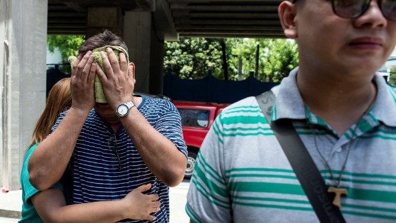 Family members of a victim cry Friday outside the Resorts World Hotel in Manila.