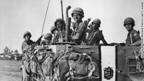 June 1967:  Israeli soldiers smile and raise their hands from the bed of a large army truck during the Six Day War at Abu Agillah in the Gaza Strip.