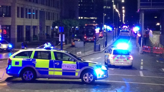 """A photograph taken on a mobile phone shows British police cars blocking the entrance to London Bridge, in central London on June 3, 2017, following an incident on the bridge.  Police are dealing with a """"major incident"""" on London Bridge, Transport for London said on Saturday, after witnesses reported seeing a van mounting the pavement and hitting pedestrians. / AFP PHOTO / Daniel SORABJI        (Photo credit should read DANIEL SORABJI/AFP/Getty Images)"""