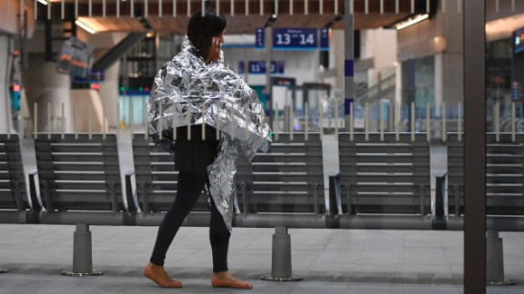 A woman wearing an emergency blanket talks on her phone at London Bridge train station. London Bridge Tube station was closed and London Bridge was closed in both directions.