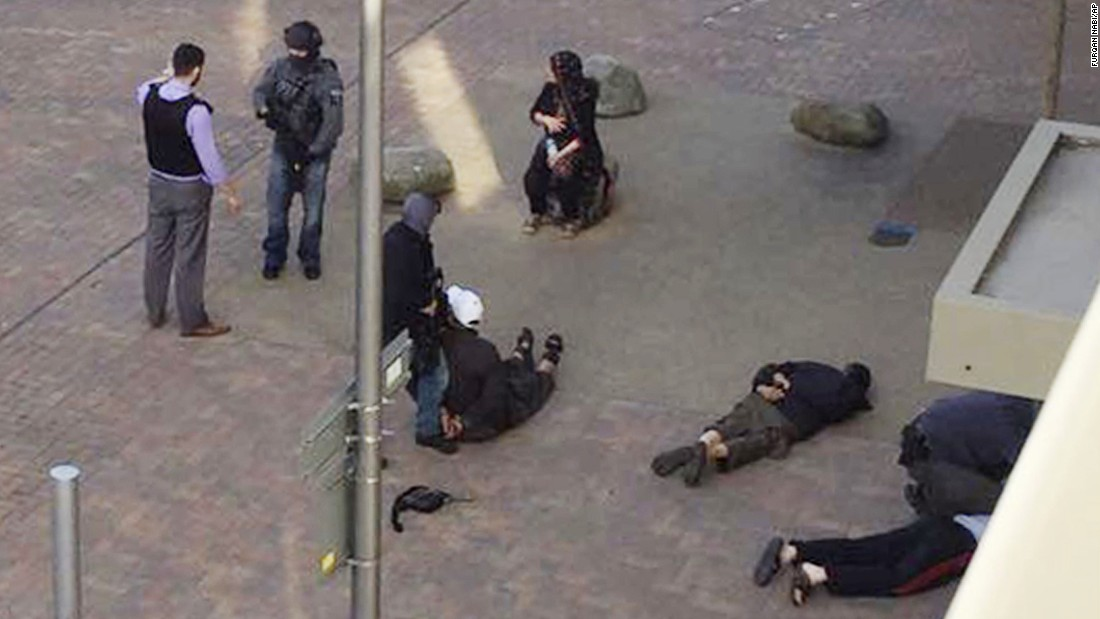 People lie on the ground after being detained by police at Elizabeth Fry apartments in Barking, east London, which officers raided Sunday, June 4, following Saturday's terror attack at London Bridge and Borough Market.