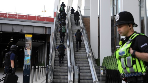 Counter terrorism officers move up an escalator under The Shard, an iconic highrise near the scene of last night