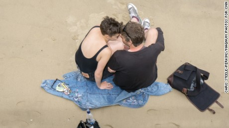 A couple on the beach by the River Thames. Many tourists and locals were going about their everyday business undaunted.