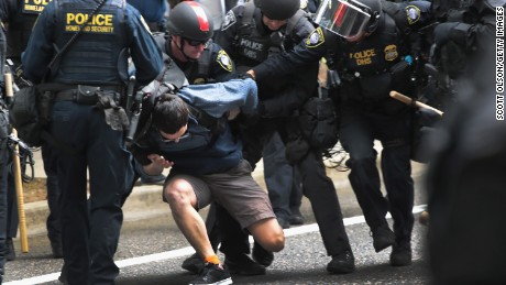 Police arrest a demonstrator during competing rallies in Portland, Oregon on Sunday.