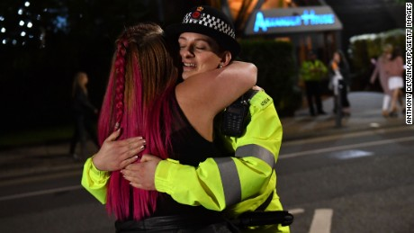 A music fan hugs a police officer as fans leave Old Trafford Cricket Ground following the One Love Manchester benefit concert for the families of the victims of the May 22, Manchester terror attack, in Greater Manchester on June 4, 2017. / AFP PHOTO / Anthony Devlin        (Photo credit should read ANTHONY DEVLIN/AFP/Getty Images)