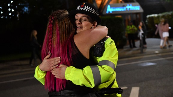A music fan hugs a police officer as fans leave Old Trafford Cricket Ground after the benefit concert for the families of the victims of the May 22, 2017 Manchester terror attack.