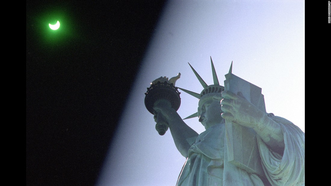 "On May 10, 1994, New Yorkers and Lady Liberty were treated to an annular solar eclipse, where the moon appears to block out the sun, apart from a ""ring of fire"" around the edges of the moon. To get this shot, the photographer held a welder's glass over the lens to protect against the intense light of the sun."