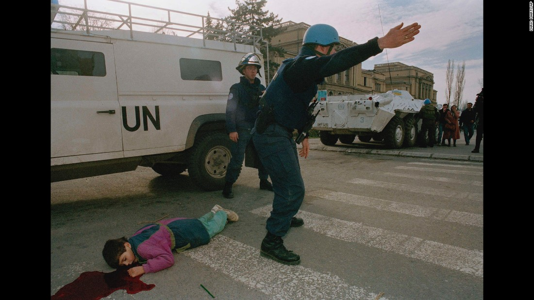 "United Nations firefighters at the scene where Nermin Divovic, 7, was shot and killed by a sniper in Sarajevo's infamous ""Sniper Alley"" on November 18, 1994. <a href=""http://www.cnn.com/2015/06/05/europe/sarajevo-then-and-now/index.html"">Sarajevo endured years of fighting during the Bosnian conflict</a>, which left more than 11,000 people dead in Sarajevo and an estimated 100,000 to 150,000 dead across the country."