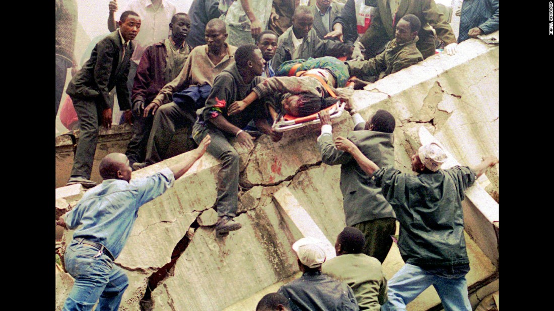 Within minutes of each other, bombs exploded outside the US embassies in Nairobi, Kenya, and Dar es Salaam, Tanzania, on August 7, 1998. In this photo of the aftermath of the Nairobi attack, rescue workers lift Susan Francisca Murianki, a US embassy worker, over the rubble of a collapsed building. The terror group al Qaeda claimed responsibility for the bombings, which left 224 dead and more than 5,000 wounded.