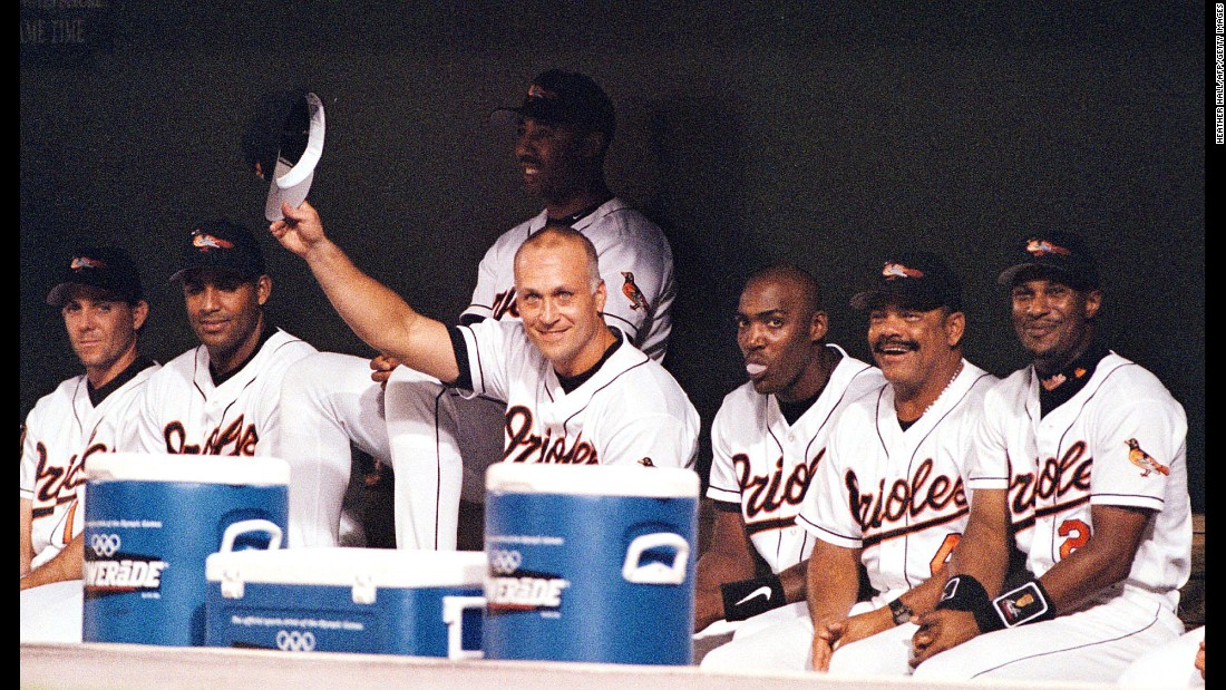 "Revered as baseball's ""Iron Man,"" Cal Ripken Jr. tips his hat to the fans at Baltimore's Camden Yards after sitting out the Orioles game on September 20, 1998. Ripken's decision not to play brought an end to his streak of 2,632 consecutive games played. The record was previously held by Lou Gehrig, who Ripken surpassed by 501 games."