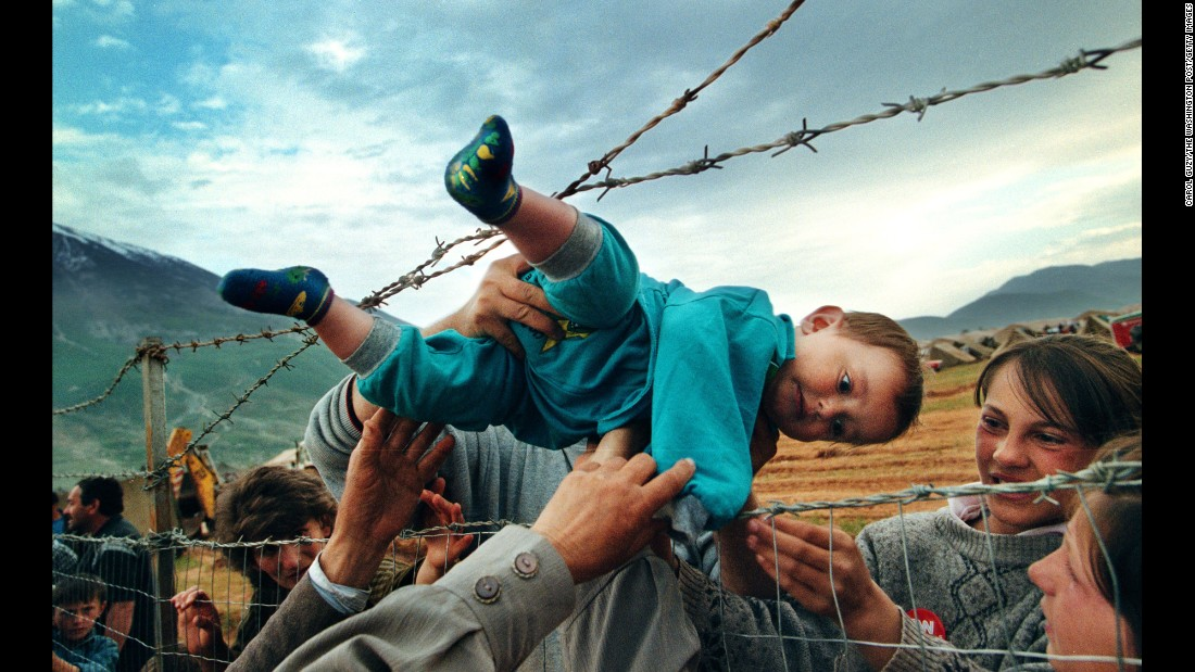 Agim Shala, a 2-year-old Kosovar refugee, is passed through a barbed-wire fence and reunited with his grandparents in a refugee camp in Kukes, Albania, on May 3, 1999. Shala's family was one of thousands driven from their homes in Kosovo by the deadly fighting in the Balkans.