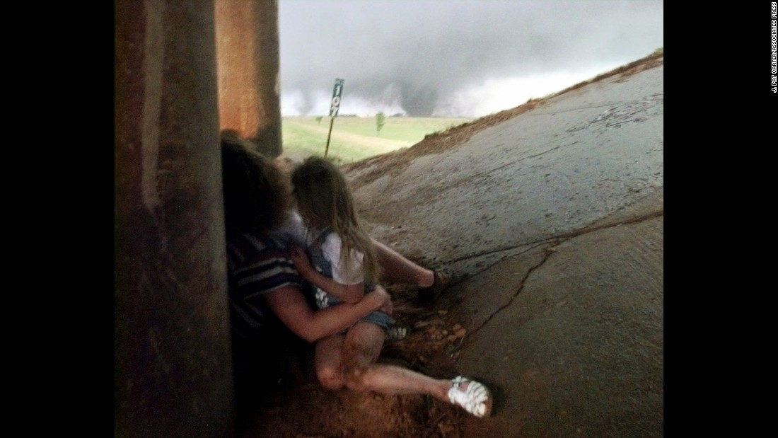 On May 3, 1999, 74 tornadoes touched down across Kansas and Oklahoma, killing 46 people and causing almost $1.5 billion in damage. The strongest tornado to form was an F-5 that ripped through Oklahoma City and its suburbs for nearly an hour and a half. Here, Tammy Holmgren and her daughters seek shelter beneath a roadway as a tornado approaches in the distance. Holmgren and her family were unharmed.