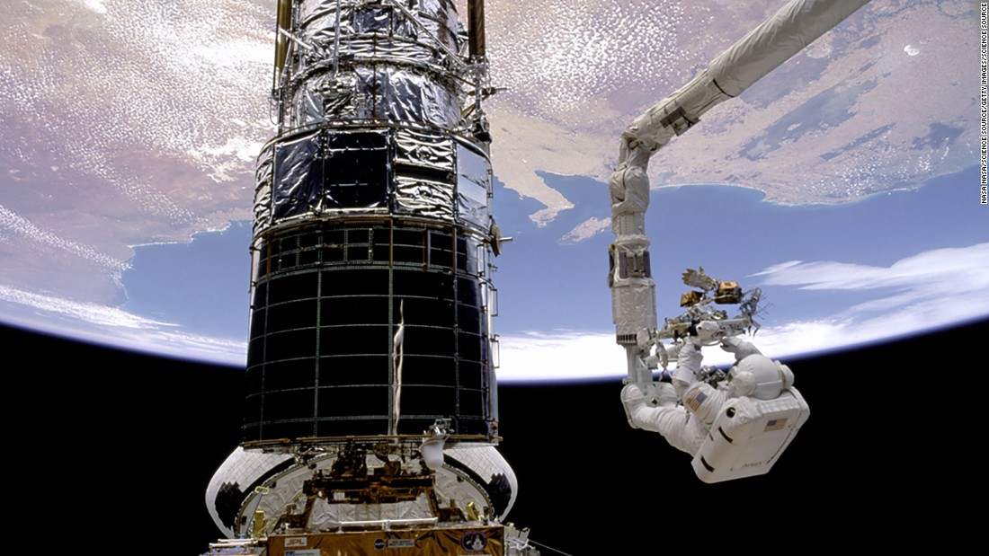"Astronaut F. Story Musgrave is hoisted to the top of the <a href=""https://www.nasa.gov/mission_pages/hubble/main/index.html"" target=""_blank"">Hubble Space Telescope</a> to install protective covers, wrapping up five days of spacewalks to repair and service the telescope in December 1993. Musgrave's handiwork has paid off for humankind; during more than a quarter-century in operation, the Hubble has beamed more than 1 million observations of our universe back to Earth."