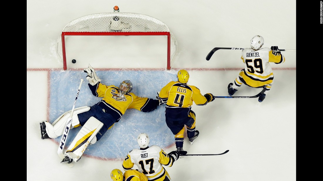 Pittsburgh forward Jake Guentzel, right, skates away after slipping the puck under Nashville goalie Pekka Rinne during Game 3 of the NHL's Stanley Cup Final on Saturday, June 3. The early goal gave Pittsburgh a 1-0 lead, but Nashville rallied for a 5-1 victory.