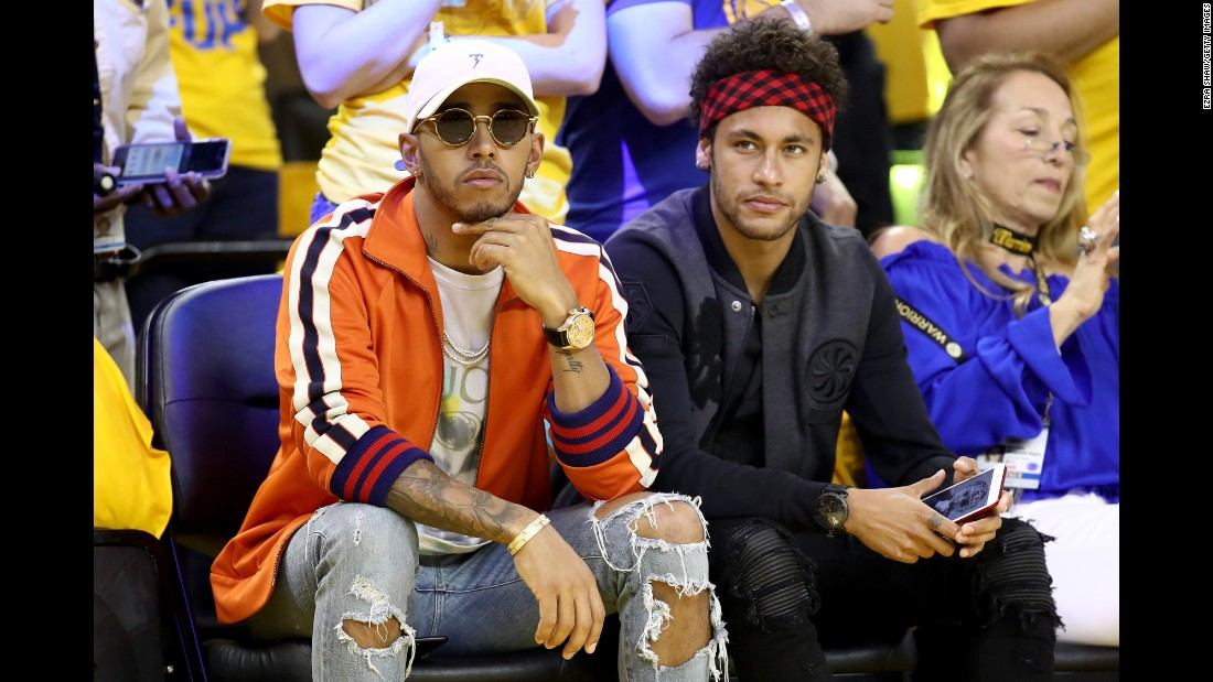 Formula One driver Lewis Hamilton, left, and Brazilian soccer star Neymar attend Game 2 of the NBA Finals on Sunday, June 4.
