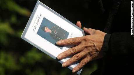 A mourner holds a program as she arrives at Christ the King Church for the funeral of Army veteran Ricky Best.