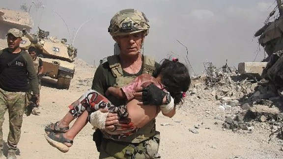 """Dave Eubank from the """"Free Burma Rangers"""" volunteer organization carries a little girl to safety after spotting her hiding under her dead mother"""