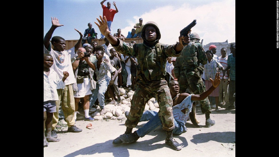 "A US soldier stands in the midst of a chaotic situation in Haiti in 1994. US troops were deployed to Haiti that year to maintain order that had steadily deteriorated since a 1991 military coup that ousted the country's first democratically elected president, <a href=""http://www.cnn.com/2013/07/18/world/jean-bertrand-aristide-fast-facts/index.html"">Jean Bertrand Aristide</a>. He was restored to power in October 1994."