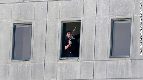 An armed man stands in a window of the Iranian parliament building on June 7.