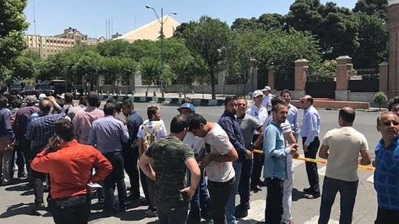 People gather Wednesday outside the parliament building in Tehran.