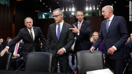 Jim Wolfe, committee staff member, left, helps direct acting FBI Director Andrew McCabe, second left, Deputy Attorney General Rod Rosenstein, and National Intelligence Director Dan Coats to their seats for a Senate Intelligence Committee hearing about the Foreign Intelligence Surveillance Act, on Capitol Hill, Wednesday. (AP Photo/Alex Brandon)