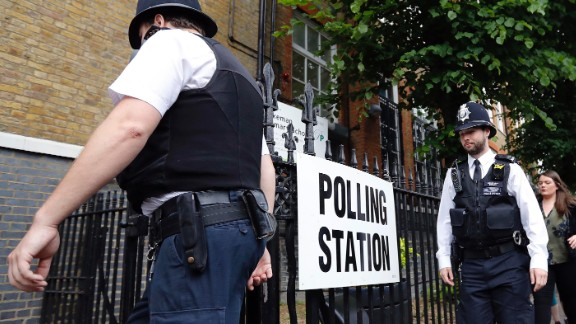 Police officers enter a polling station in London ahead of the arrival of Labour Party leader Jeremy Corbyn.