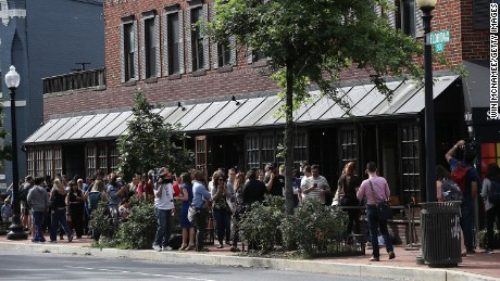 "People line up outside Shaw's Tavern to watch former FBI Director James Comey testify before the Senate Intelligence Committee June 8, 2017 in Washington, DC.  Shaw's Tavern announced early in the week that In honor of the hearing the bar would host a ""covfefe"" and offer $5 Russian vodka flavors and $10 ""FBI"" sandwiches."