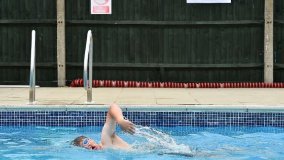 A swimmer does laps at a public pool where a polling station was set up in Arundel, England.