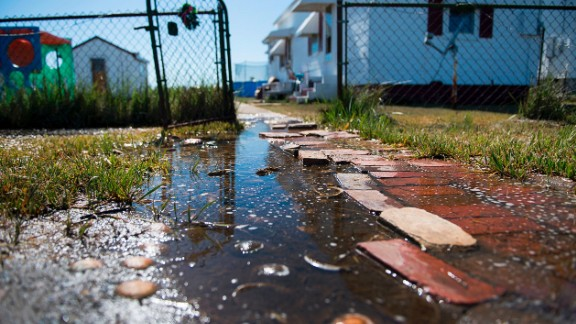 "Sea water collects in front of a home in Tangier, Virginia, in May 2017. Tangier Island in Chesapeake Bay has lost two-thirds of its landmass since 1850. Now, the 1.2 square mile island is suffering from floods and erosion and is slowly sinking. A paper published in the journal Scientific Reports states that ""the citizens of Tangier may become among the first climate change refugees in the continental USA."""