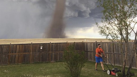 """Cecilia Wessels posted to Facebook this photo of her husband, Theunis, mowing their yard in the town of Three Hills in Alberta, Canada, on Friday, June 2. The photo shows a tornado looming over Theunis in the background. """"Yes, he did know it was there,"""" Cecilia Wessels told CNN. """"He told me, 'I'm keeping an eye on it.' """""""