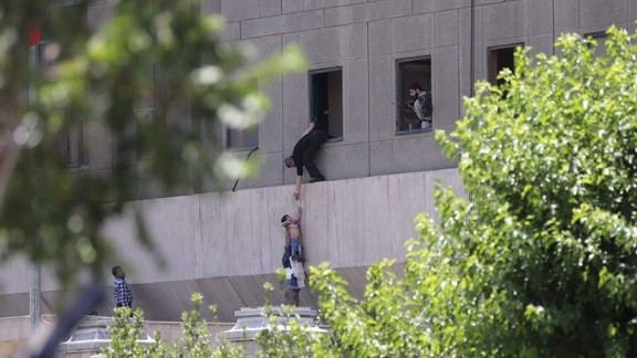 Police help civilians escape the Parliament building in Tehran, Iran, on Wednesday, June 7, during twin attacks. At least 12 people were killed when six attackers mounted simultaneous gun and suicide bomb assaults on Iran's Parliament building and the tomb of the republic's revolutionary founder, in one of the most audacious assaults to hit Tehran in decades. Iran's Revolutionary Guards said Saudi Arabia supported ISIS in the deadly twin attacks.
