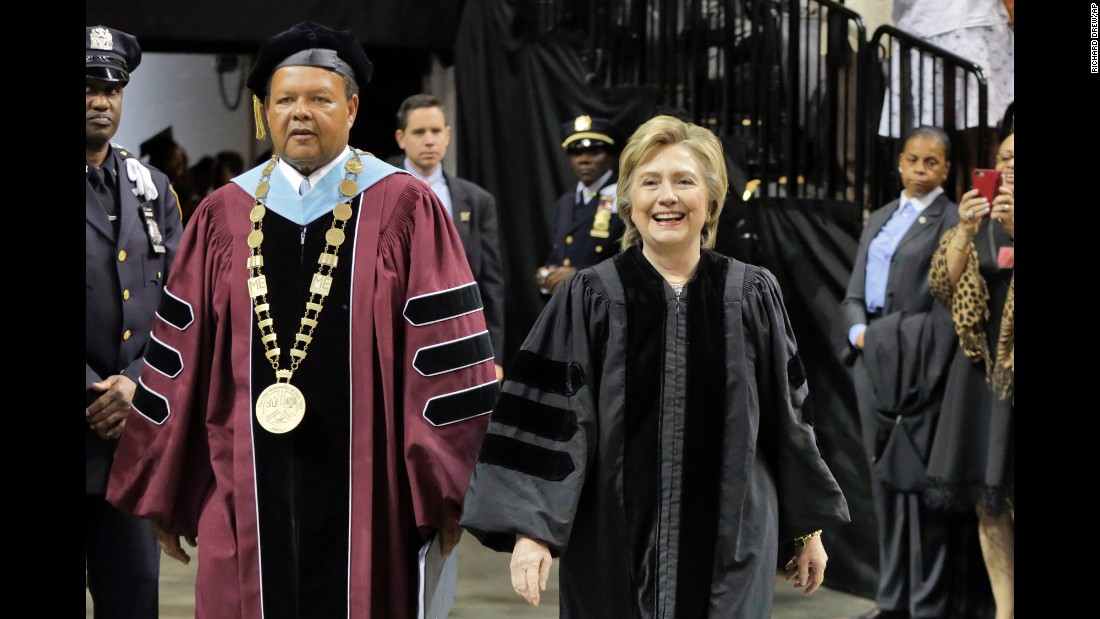 Former Secretary of State Hillary Clinton arrives for the Medgar Evers College commencement with Dr. Rudolph Crew, president of the college, in Brooklyn, New York, on Thursday, June 8. Clinton delivered the commencement address.