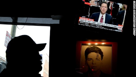 SAN FRANCISCO, CA - JUNE 08:  A patron at Ace's Bar watches a television broadcast of former FBI Director James Comey testify before the Senate Intelligence Committee on June 8, 2017 in San Francisco, California. People across the country are flocking to bars and restaurants to watch former FBI director as he testifies before the Senate Intelligence Committee about his conversations with U.S. President Donald Trump.  (Photo by Justin Sullivan/Getty Images)