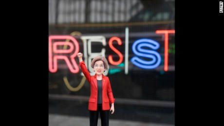 The Elizabeth Warren action figure raises her fist in the air.