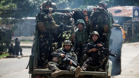 Soldiers aboard their vehicles maneuver through a street in Marawi on Saturday.