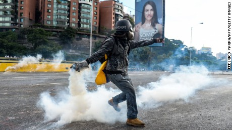 "An opposition demonstrator throws a molotov cocktail in a clash with riot police during the ""Towards Victory"" protest against the government of Nicolas Maduro, in Caracas on June 10, 2017.  Clashes at near daily protests by demonstrators calling for Maduro to quit have left 66 people dead since April 1, prosecutors say."