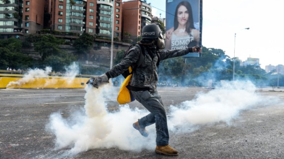 """An opposition demonstrator throws a molotov cocktail in a clash with riot police during the """"Towards Victory"""" protest against the government of Nicolas Maduro, in Caracas on June 10, 2017. Clashes at near daily protests by demonstrators calling for Maduro to quit have left 75 people dead since April 1, prosecutors say."""