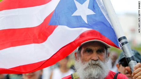 A man carries a Puerto Rican flag during a protest against the referendum for Puerto Rico political status in San Juan, on June 11, 2017. To become a true US state, to choose independence or to maintain the status quo: Puerto Ricans went to the polls to consider their political future in a non-binding referendum many have vowed to boycott. / AFP PHOTO / Ricardo ARDUENGO        (Photo credit should read RICARDO ARDUENGO/AFP/Getty Images)