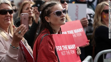 Attendees hold placards while listening to Jeremy Corbyn, leader of the UK opposition Labour Party, speak during a campaign rally in Watford one day before the general election.