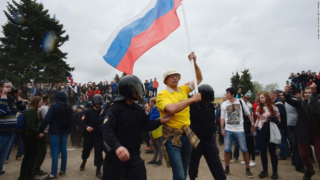 Russian police officers detain a flag-waving rally  participant in Saint Petersburg.